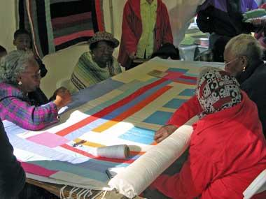 Women from Gees Bend work on a quilt